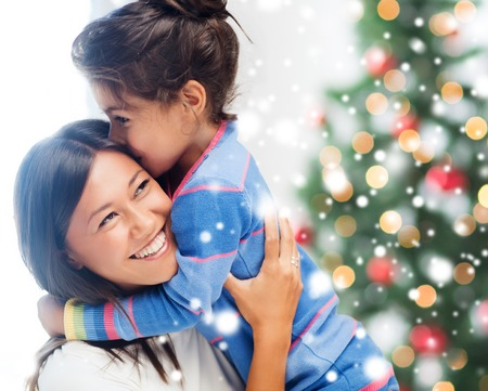 asian trees: childhood, happiness, christmas, family and people concept - smiling little girl and mother hugging indoors