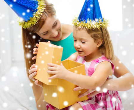 family, childhood, holidays and people concept - happy mother and daughter in blue party hats with gift box photo