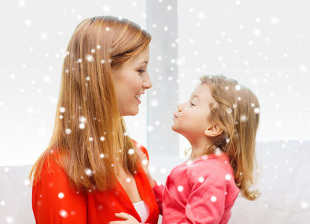 family, childhood, holidays and people concept - happy mother and daughter kissing at home photo