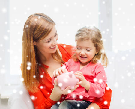 family, childhood, holidays, finances and people concept - happy mother and daughter with piggy bank photo