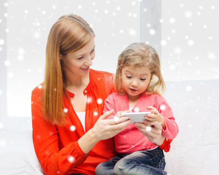 family, childhood, holidays, technology and people concept - happy mother and daughter with smartphone at home photo