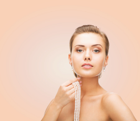 string of pearls: beauty, people and jewelry concept - beautiful woman with pearl earrings and necklace over beige background