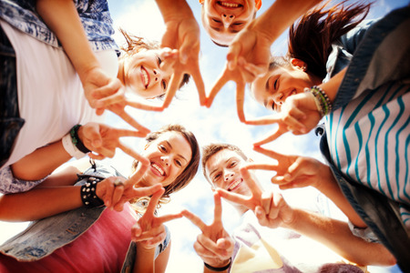 man holding sign: summer holidays and teenage concept - group of teenagers showing finger five gesture