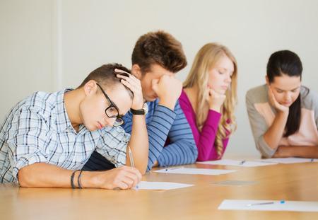 onderwijs, school, testen en mensen concept - groep studenten met papieren te denken of het maken van testen Stockfoto