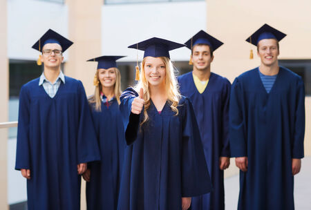 education, graduation, gesture and people concept - group of smiling students in mortarboards and gowns showing thumbs up outdoors photo