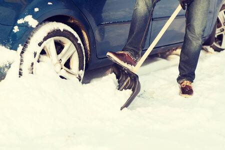 stuck up: transportation, winter and vehicle concept - closeup of man digging up stuck in snow car