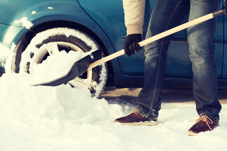 transportation, winter and vehicle concept - closeup of man digging up stuck in snow car photo