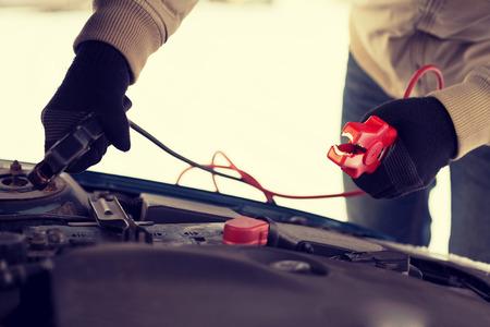 bateria: el transporte, el invierno y el concepto de vehículo - de cerca del hombre bajo el capó con cables de arranque Foto de archivo