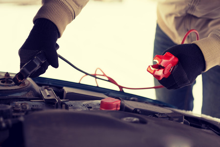 vervoer, winter en concept voertuig - close-up van de mens onder de motorkap met startkabels Stockfoto