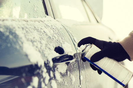 winterly: transportation, winter and vehicle concept - closeup of man hand with lock door de-icer