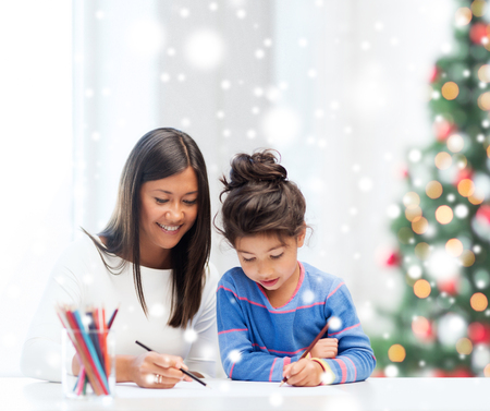 asian trees: childhood, family, christmas and people concept - smiling little girl and mother or teacher drawing with coloring pencils indoors Stock Photo