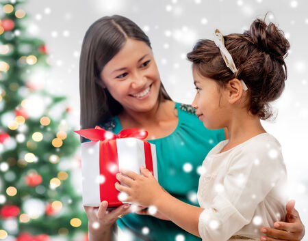 christmas, holidays, family and people concept - happy mother and child girl with gift box at home photo