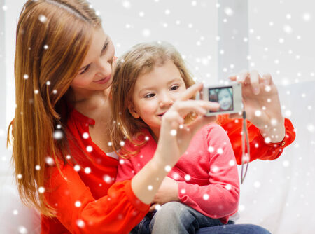 family, childhood, holidays, technology and people concept - smiling mother taking picture of daughter with digital camera at home photo
