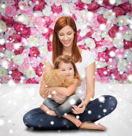 children playing with toys: childhood, parenting and people concept - happy mother with little girl and teddy bear toy over wooden floor and flowers background