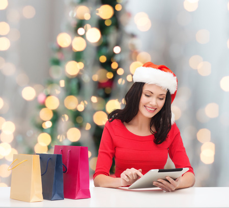 christmas, technology and people concept - smiling woman in santa helper hat with shopping bags and tablet pc computer over tree lights background photo