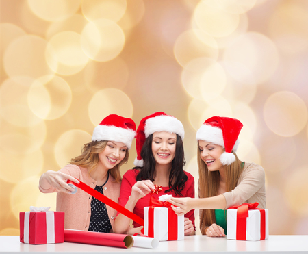christmas, holidays, celebration, decoration and people concept - smiling women in santa helper hats with decorating paper and gift boxes over beige lights background photo