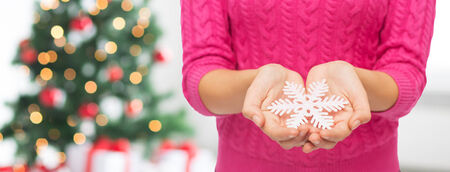 christmas, holidays and people concept - close up of woman in pink sweater holding snowflake over living room and tree background photo