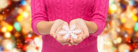 christmas, holidays and people concept - close up of woman in pink sweater holding snowflake over red lights background photo