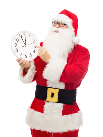 12 oclock: christmas, holidays and people concept - man in costume of santa claus with clock showing twelve pointing finger