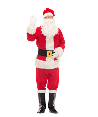 christmas, holidays, gesture and people concept - man in costume of santa claus waving hand photo