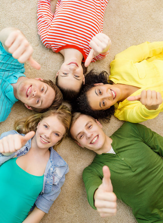 education and happiness concept - group of young smiling people lying down on floor in circle and showing thumbs up photo