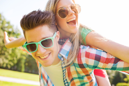 holidays, vacation, love and friendship concept - smiling teen couple in sunglasses having fun in summer park photo