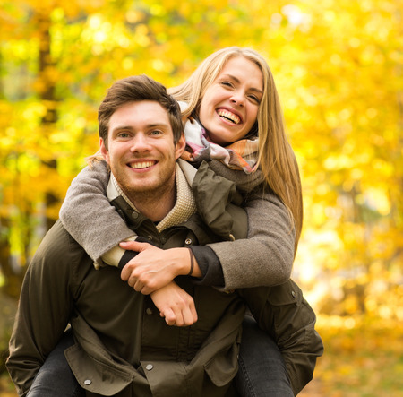 love, relationship, family and people concept - smiling couple having fun in autumn park Stockfoto