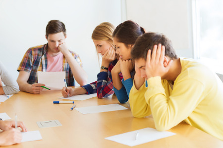 stress test: education, school, test and people concept - group of students with papers thinking or making test