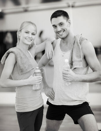 couple exercising: fitness, sport, training, gym and lifestyle concept - two smiling people in the gym