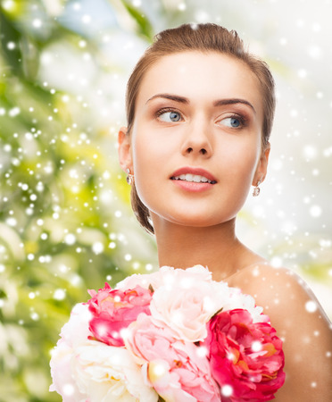 girl with rings: beauty, holidays, people and jewelry - woman with diamond earrings, ring and flower Stock Photo