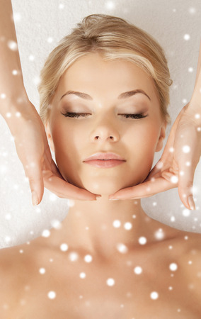 beauty, health, holidays, people and spa concept - beautiful\ woman in spa salon getting face or head massage