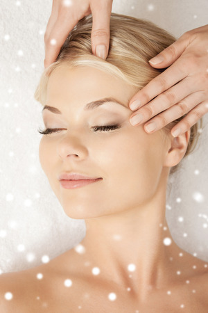 closed eye: beauty, health, holidays, people and spa concept - beautiful woman in spa salon getting face or head massage Stock Photo