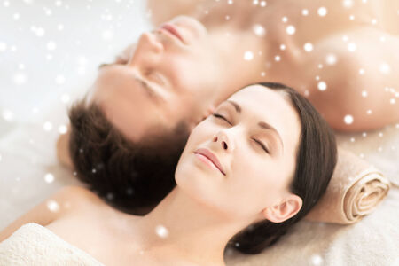 beauty, health, holidays, people and spa concept - happy couple with closed eyes lying in spa salon photo
