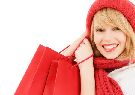 woman bag: happiness, winter holidays, christmas and people concept - smiling young woman in hat and scarf with red shopping bags over white background
