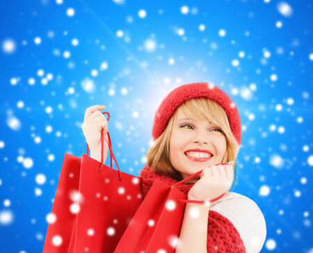 christmas shopping bag: happiness, winter holidays, christmas and people concept - smiling young woman in hat and scarf with shopping bags over blue snowy background Stock Photo
