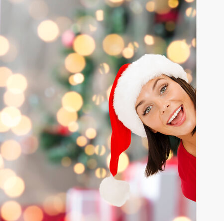 christmas, x-mas, people, advertisement and sale concept - happy woman in santa helper hat with blank white board over tree lights background photo