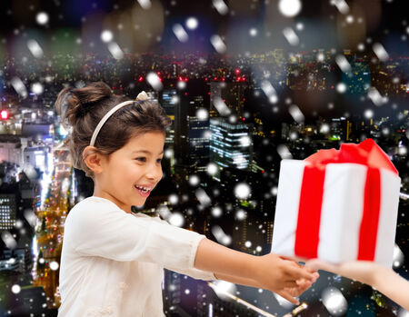 holidays, presents, christmas, childhood and people concept - smiling little girl with gift box over snowy night city background photo