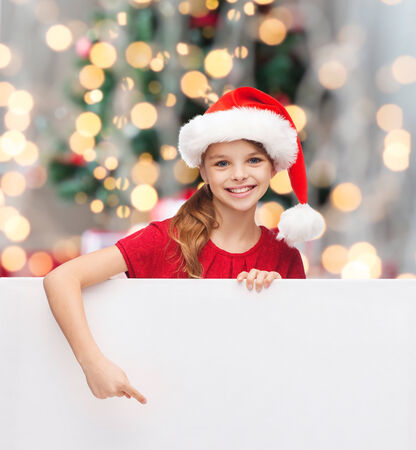 christmas, holidays, people, advertisement and sale concept - happy little girl in santa helper hat with blank white board over tree lights background photo