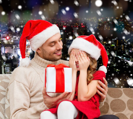 gift giving: family, christmas, winter holidays and people concept - smiling daughter with closed eyes waiting for present from father over snowy night city background