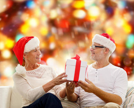 family, holidays, christmas, age and people concept - happy senior couple in santa helper hats with gift box over red lights background photo