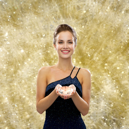 people, christmas, winter holidays and glamour concept - smiling woman in evening dress with diamond over yellow lights background photo