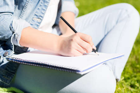 body writing: lifestyle, summer vacation, education and people concept - close up ofyoung girl writing with pencil to notebook and sitting on grass in park Stock Photo
