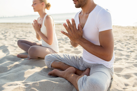 fitness, sport, people and lifestyle concept - close up of couple making yoga exercises sitting on pier outdoors photo