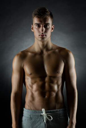 male torso: sport, bodybuilding, strength and people concept - young man standing over black background