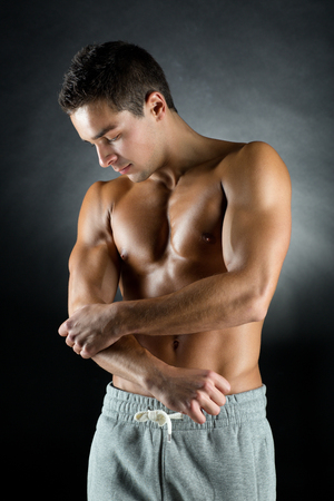 tense: pain relief, sport, bodybuilding, health and people concept - young man standing over black background Stock Photo