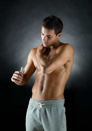 sport, bodybuilding, medicine and people concept - young man standing over black background and applying pain relief gel on his shoulder photo