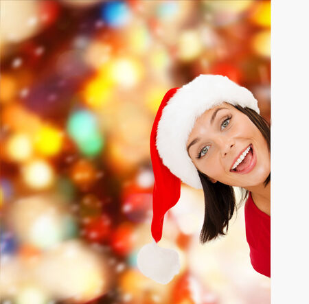 christmas, x-mas, people, advertisement and sale concept - happy woman in santa helper hat with blank white board over red lights background photo