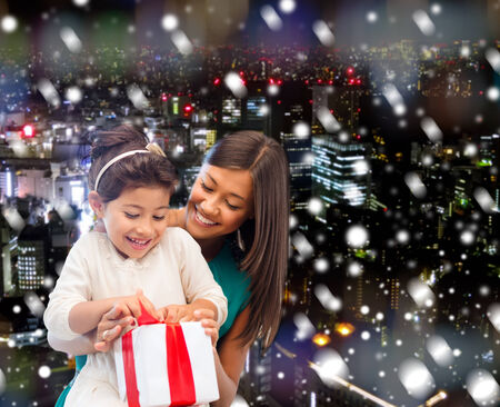 christmas, holidays, celebration, family and people concept - happy mother and little girl with gift box over snowy night city background photo