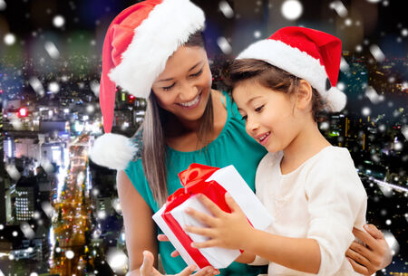 christmas, holidays, celebration, family and people concept - happy mother and little girl in santa helper hats with gift box over snowy night city background photo