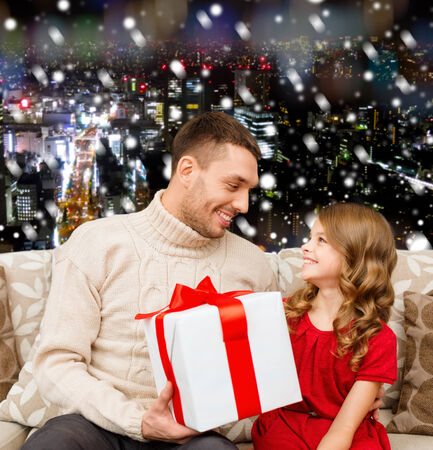 family, christmas, holidays and people concept -smiling father and daughter with gift box over snowy night city background photo